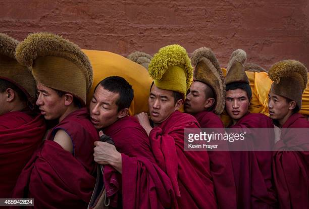 Tibetan Buddhist Monks of the Gelug or Yellow Hat order carry a large thangka of Buddha after showing it to worshippers during Monlam or the Great...