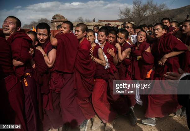 Tibetan Buddhist Monks of the Gelug or Yellow Hat school carry a rolled up giant thangka before unfurling it on a mountain side at the Rongwo...