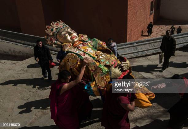 Tibetan Buddhist Monks of the Gelug or Yellow Hat school carry large Buddha to a temple for blessings at the Labrang Monastery during Monlam or the...