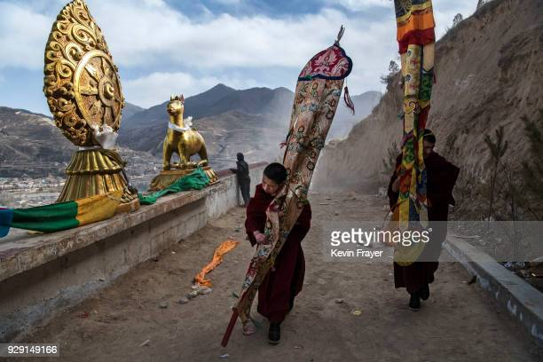 Tibetan Buddhist Monks of the Gelug or Yellow Hat school struggle in the wind as they leave after unfurling a giant thangka on a mountain side at the...