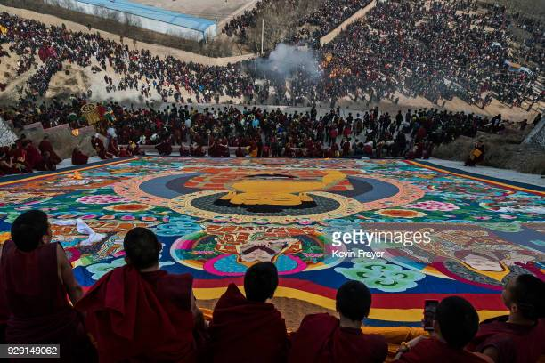 Tibetan Buddhist Monks of the Gelug or Yellow Hat school unveil a giant thangka showing the Buddha on a hillside near the Rongwo Monastery during...