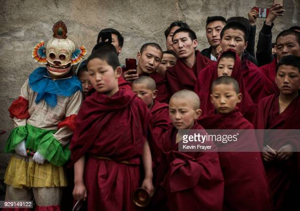 Tibetan Buddhist Monks of the Gelug or Yellow Hat school watch rituals following a Cham dance at the Rongwo Monastery during Monlam or the Great...