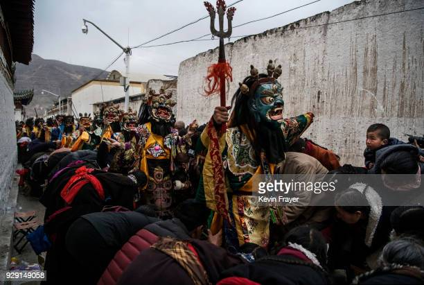 Tibetan Buddhist Monks of the Gelug or Yellow Hat school wear masks as they bless worshippers during a Cham dance at the Rongwo Monastery during...