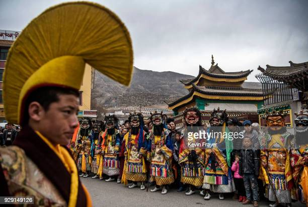 Tibetan Buddhist Monks of the Gelug or Yellow Hat school wear masks as as they lineup in a procession following a Cham dance at the Rongwo Monastery...
