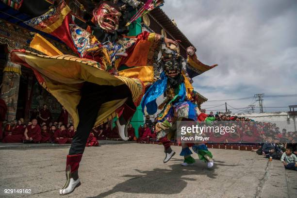 Tibetan Buddhist Monks of the Gelug or Yellow Hat school wear masks as perform during a Cham dance at the Rongwo Monastery during Monlam or the Great...