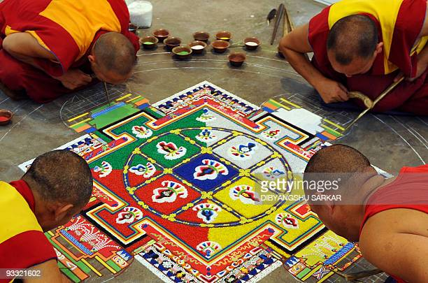 Tibetan Buddhist monks prepare a mandala religious artwork made from coloured sand during an exhibition at the Thank You India Festival in Bangalore...