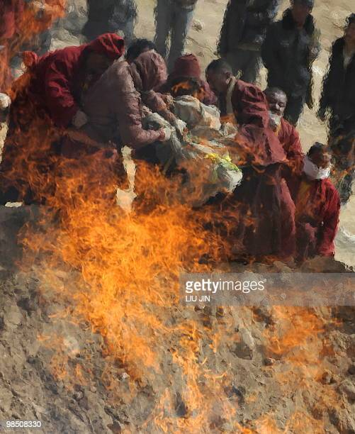 Tibetan Buddhist monks prepare to throw the body of an earthquake victim the fire of a mass cremation on a hillside in Jiegu, Yushu County, on April...