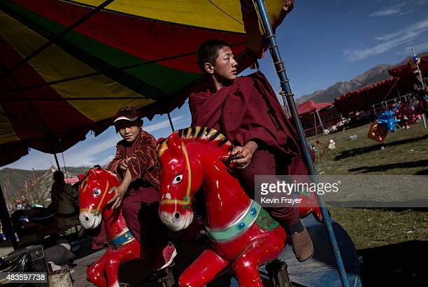 Tibetan Buddhist monks sit on a carousel at a local festival on July 26 2015 on the Tibetan Plateau in Yushu County Qinghai China Tibetan nomads face...