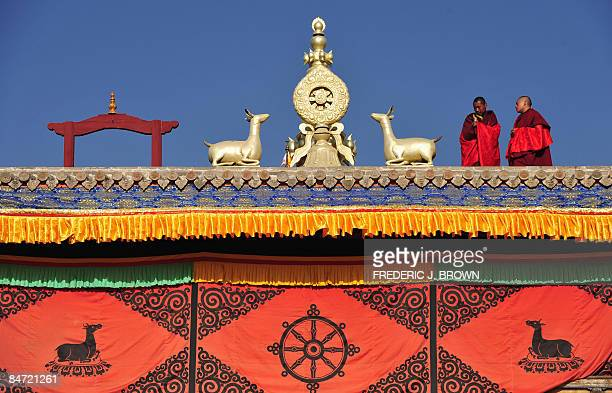 Tibetan Buddhist monks stand on a rooftop ahead of celebrations for Monlam or the Great Prayer Festival at the Nyentog Monastery also known as...