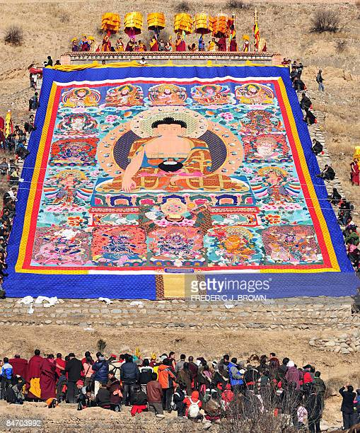 Tibetan Buddhist monks unfurl a huge thanka showing the image of Sakyamuni the founder of Buddhism from a hillside during the Sunning of the Buddha...