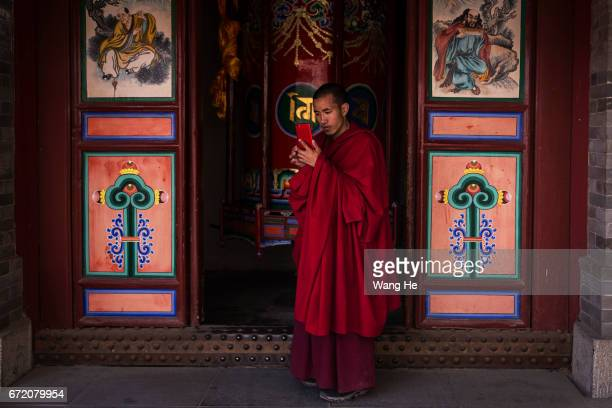 Tibetan Buddhist monks use iphone in the courtyard of the Kumbum Monastery on April 23 2017 in Xining Qinghai Province Kumbum was founded in 1583 in...