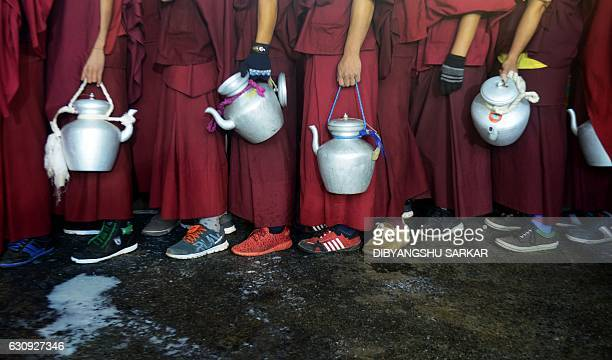 TOPSHOT Tibetan Buddhist monks wait to collect boiling milk to distribute to devotees who are participating in a special religious prayer attended by...