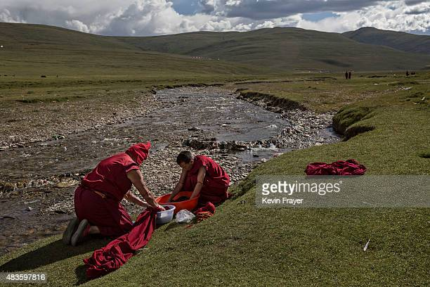 Tibetan Buddhist monks wash clothing at a monastery next to a government resettlement community for former nomads on July 23 2015 on the Tibetan...