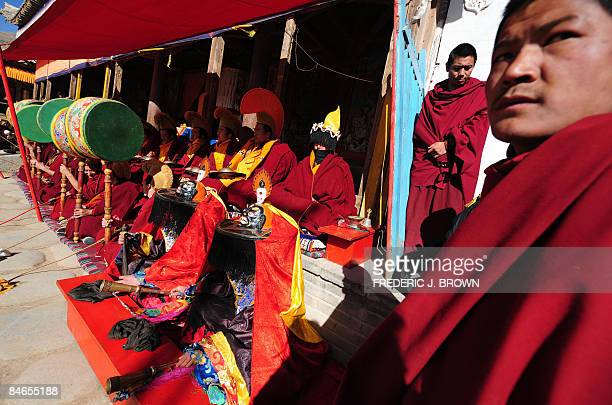 Tibetan Buddhist monks watch as other provide the music for Cham Dances during ongoing festivities celebrating Monlam or the Great Prayer Festival at...