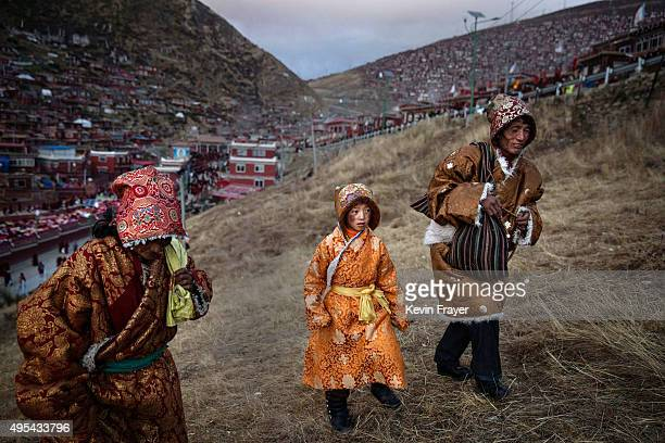 Tibetan Buddhist nomad family walks on a hillside follwong prayers at the annual Bliss Dharma Assembly at the Larung Wuming Buddhist Institute on...