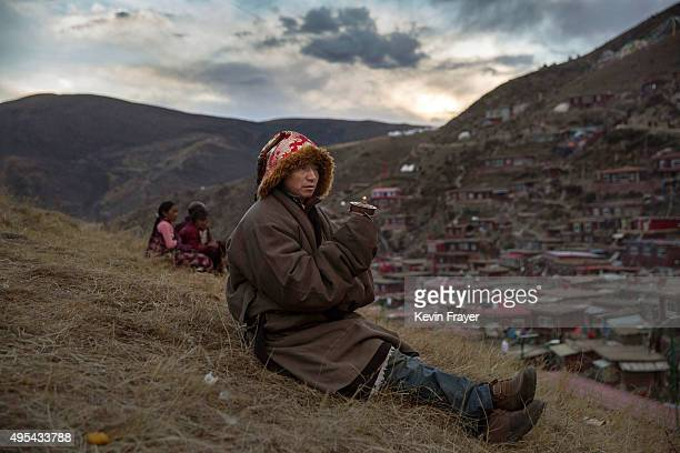 Tibetan Buddhist nomad spins a prayer wheel, or mani khor-lo, as he sits on a hillside during the annual Bliss Dharma Assembly at the Larung Wuming...