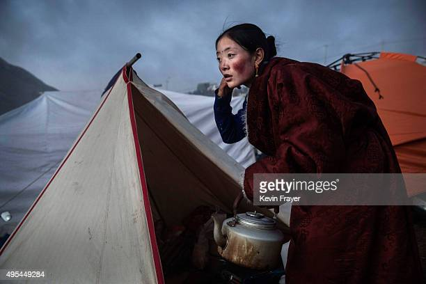 Tibetan Buddhist nomad woman prepares tea at dusk following a chanting session as part of the annual Bliss Dharma Assembly at the Larung Wuming...