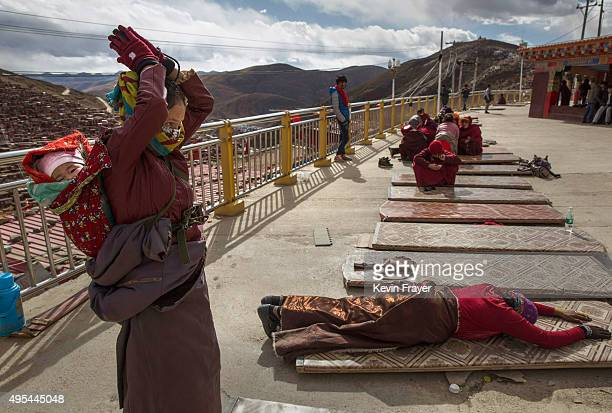Tibetan Buddhist nomad woman prostrates at a monastery during the annual Bliss Dharma Assembly at the Larung Wuming Buddhist Institute on October 30...