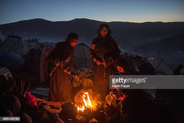 Tibetan Buddhist nomads cook and stay warm by candlelight at dusk following a chanting session as part of the annual Bliss Dharma Assembly at the...