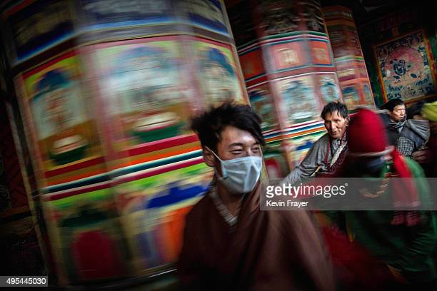 Tibetan Buddhist nomads rush passed a large prayer wheel outside the annual Bliss Dharma Assembly at the Larung Wuming Buddhist Institute on October...