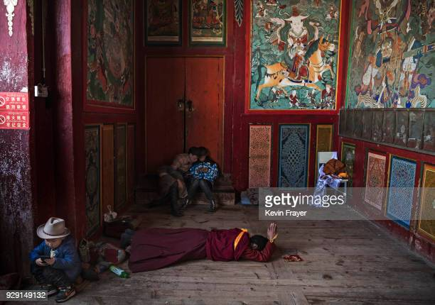 Tibetan Buddhist nun of the Gelug or Yellow Hat school prostrates in prayer as children play on mobile phones at the Rongwo Monastery during Monlam...