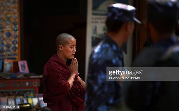 A Tibetan Buddhist nun prays at the Bouddhanath Stupa as Nepalese security force personnel stand guard during the 54th anniversary of the 1959...