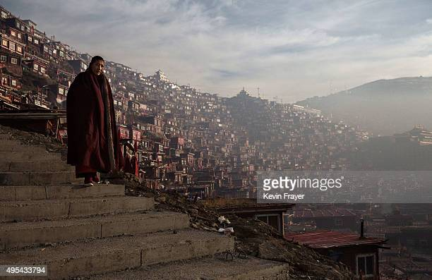 Tibetan Buddhist nun walks passed dwellings on her way to a chanting session as part of the annual Bliss Dharma Assembly at the Larung Wuming...