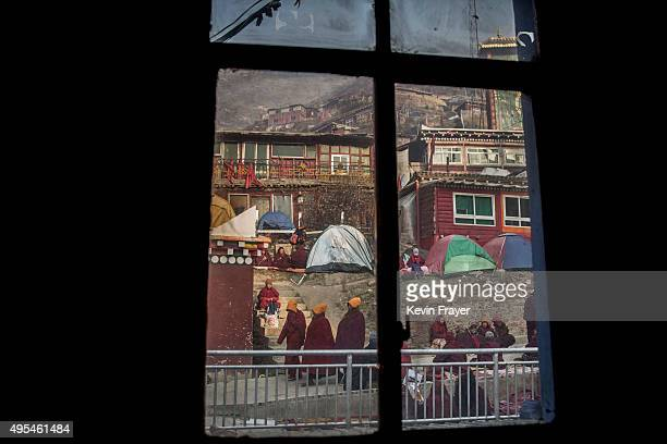 Tibetan Buddhist nuns are seen through a window on the way to a morning chanting session at the annual Bliss Dharma Assembly at the Larung Wuming...