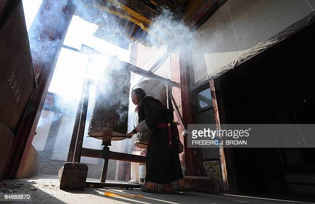 A Tibetan Buddhist pilgrim spins a prayer wheel at the Kumbum Monastery outside of Xining on February 7 2009 in northwest China's Qinghai province on...
