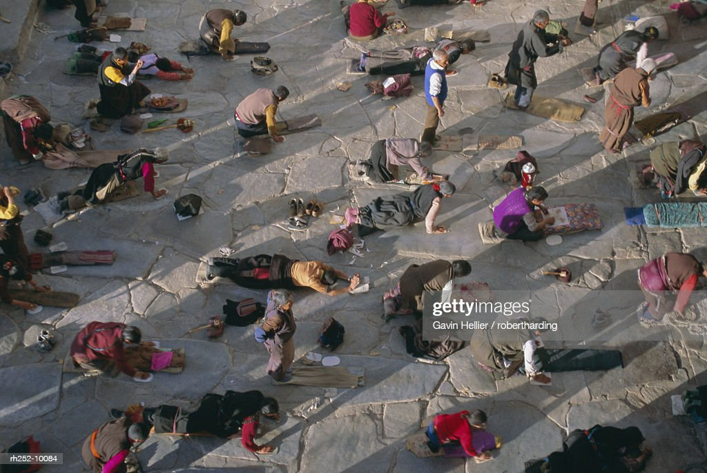 Tibetan Buddhist pilgrims prostrating outside the Jokhang Temple, Lhasa, Tibet, China, Asia : Foto de stock