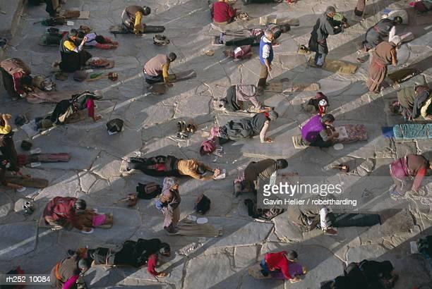 tibetan buddhist pilgrims prostrating outside the jokhang temple, lhasa, tibet, china, asia - 巡礼 ストックフォトと画像