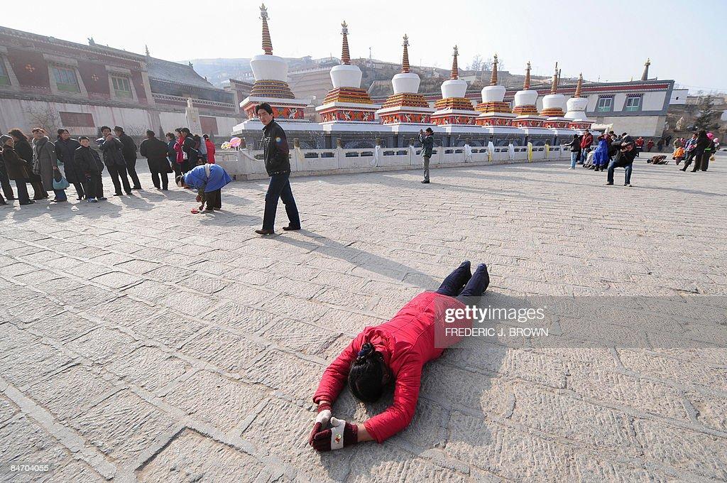A Tibetan Buddhist prostrates herself in : News Photo