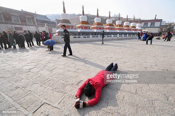 A Tibetan Buddhist prostrates herself in prayer past a row of stupas while making her clockwise circular trek around the Kumbum Monastery outside of...