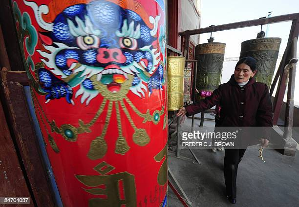 A Tibetan Buddhist spins a prayer wheel at the Kumbum Monastery outside of Xining on February 7 2009 in northwest China's Qinghai province on the...