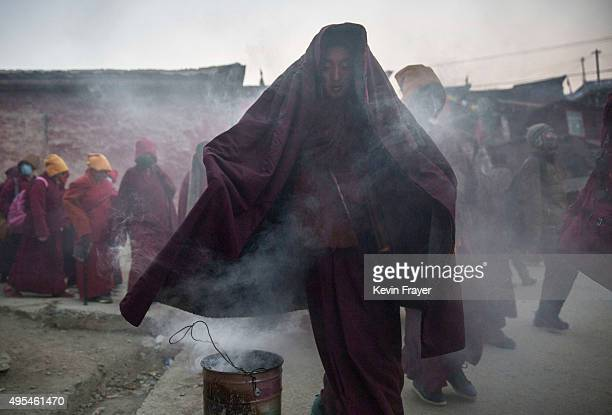 Tibetan Buddhist walks through smoke froom juniper bruned as a blessing on his way to a morning chanting session at the annual Bliss Dharma Assembly...