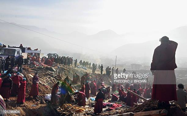 Tibetan Buddhist watches others prepare the scene of a mass cremation on a hillside in Jiegu, Yushu County, on April 17, 2010. China began the mass...