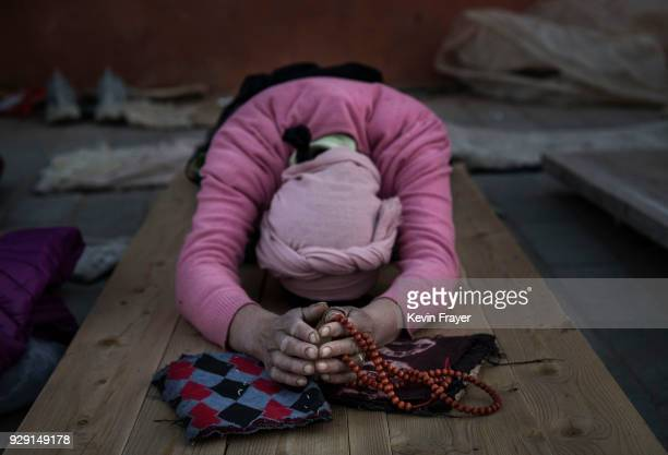 Tibetan Buddhist woman prostrates at the Labrang Monastery during Monlam or the Great Prayer on February 27 2018 in Xiahe county Gannan Tibetan...