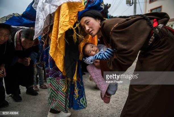 Tibetan Buddhist women holds her baby as she leans over to be blessed by Monks of the Gelug or Yellow Hat school during a Cham dance at the Rongwo...
