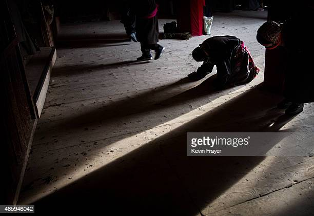 Tibetan Buddhist women pray at the entrance to a temple during Monlam or the Great Prayer rituals on March 5 2015 at the Labrang Monastery Xiahe...