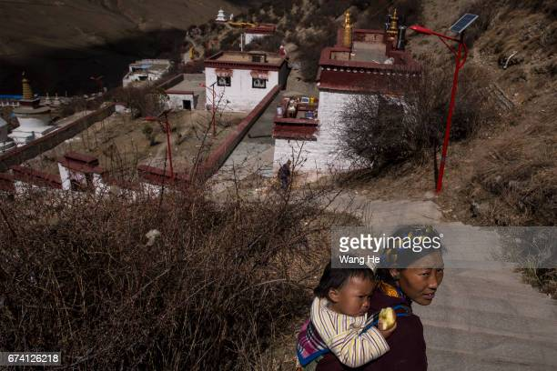 Tibetan buddhist worshipper carrying a child walks around the courtyard of the Drak Yerpa on April 27 2017 in LhasaTibet Autonomous Region China Drak...
