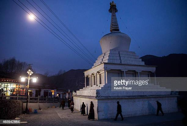 Tibetan Buddhists make Kora around a stupa as they pray during Monlam or the Great Prayer rituals on March 3 2015 at the Labrang Monastery Xiahe...