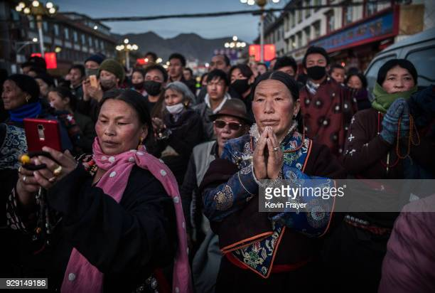 Tibetan Buddhists pray and watch a broadcast of the butterlamp rituals outside the Labrang Monastery during Monlam or the Great Prayer on March 2...