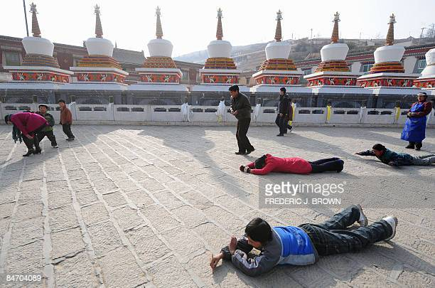 Tibetan Buddhists prostrate themselves in prayer past a row of stupas while making their clockwise circular trek around the Kumbum Monastery outside...