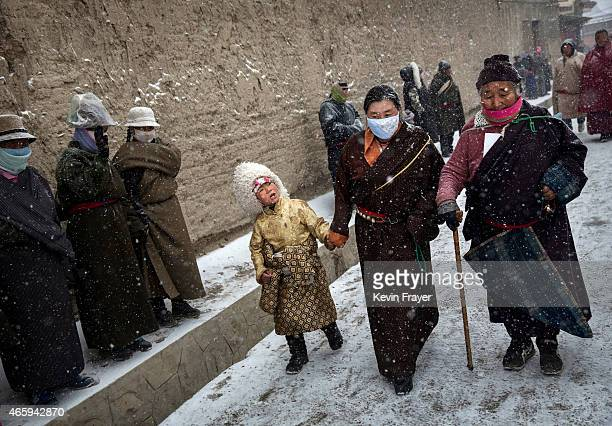 Tibetan Buddhists walk in the snow at a procession during Monlam or the Great Prayer rituals on March 4 2015 at the Labrang Monastery Xiahe County...
