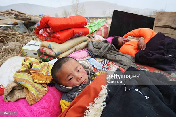 Tibetan child and his father sleep outside under blankets following a strong earthquake, on April 16 in Jiegu, near Golmud, China. It is currently...