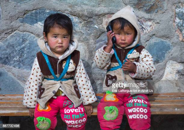 tibetan Children sit on a bench and playing with a mobile phone Gansu province Labrang China on October 31 2017 in Labrang China
