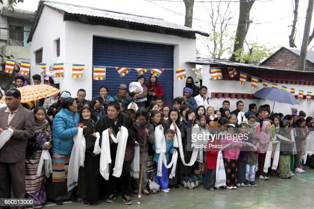 Tibetan devotees wait with ceremonial scarves to greet their spiritual leader the Dalai Lama as he leaves after attending a function at the...