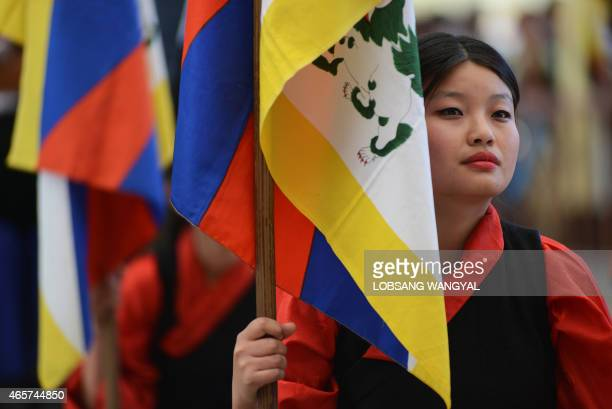 A Tibetan exile holds the national flag as she listens to a speech by the Sikyong or Prime Minister of the exiled Central Tibetan Administration...