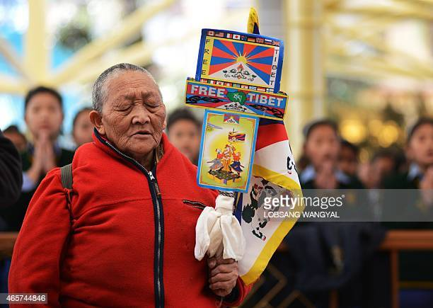 A Tibetan exile prays during a speech by the Sikyong or Prime Minister of the exiled Central Tibetan Administration Lobsang Sangay during an event...