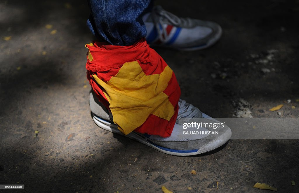 A Tibetan exile residing in India wears a Chinese national flag on his shoe as he participates in a protest rally in New Delhi on March 10, 2013. The protest marked the 54th anniversary of the Tibetan national uprising, the 1959 rebellion against China's rule in Tibet. AFP PHOTO/ Sajjad Hussain